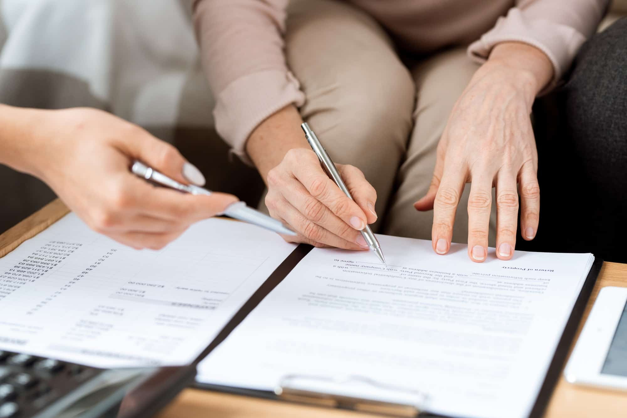 Hands of mature client and real estate agent with pens pointing at contract
